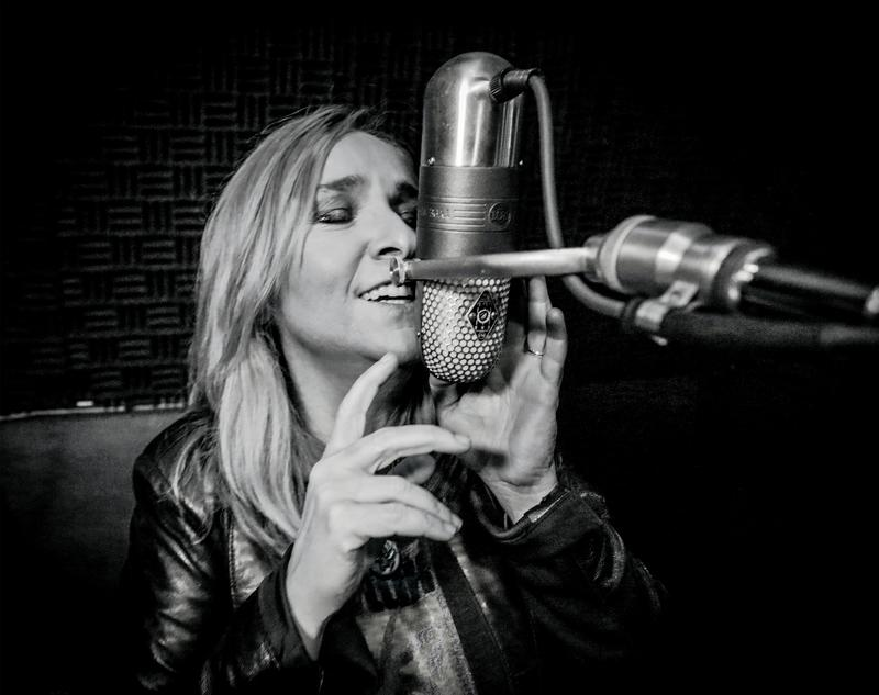 Melissa Etheridge sings into a classic microphone
